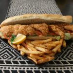 "Freshly fried catfish stacked on fresh French bread. Served ""dressed"" with lettuce, tomato, and pickles with a choice of regular or chipotle mayonnaise."